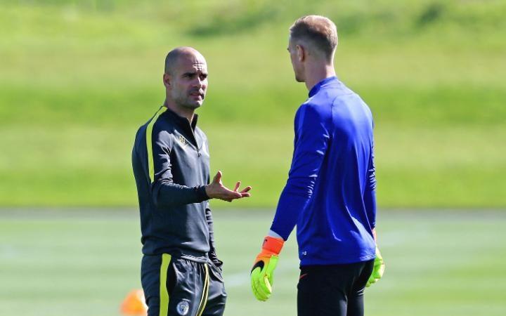 Josep Guardiola habla con el portero Joe Hart durante un entrenamiento del Manchester City.