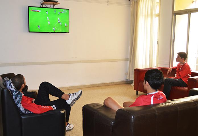 Tres alumnos miran un partido de fútbol en una residencia Marcet.
